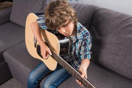 Photo pour Portrait de peu concentré garçon jouant de la guitare acoustique à la maison - image libre de droit