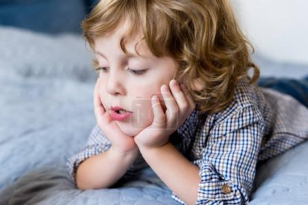 Photo for Close-up portrait of adorable pensive little boy lying on bed - Royalty Free Image