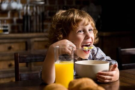 Photo for Cheerful little boy eating breakfast and looking away - Royalty Free Image
