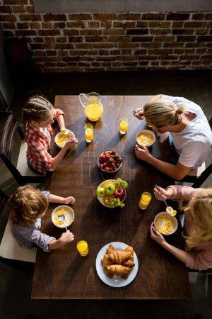 Photo pour Vue aérienne de la famille avec deux enfants qui prennent le petit déjeuner à la maison - image libre de droit