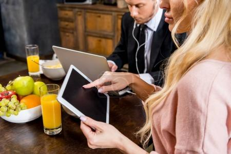 Photo for Cropped shot of young couple using gadgets during breakfast - Royalty Free Image