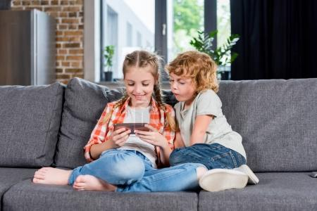 Photo for Adorable smiling kids using smartphone while sitting together on sofa - Royalty Free Image