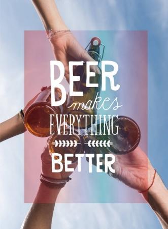 Photo pour Vue à angle bas de jeunes amis cliquetis bouteilles de bière à l'extérieur - image libre de droit