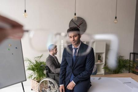 Foto de Enfoque selectivo del empresario afroamericano pensativo mirando a cámara mientras colega discapacitado sentado en el lugar de trabajo en oficina - Imagen libre de derechos