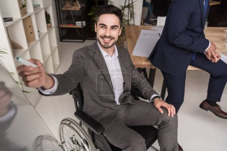 disabled businessman pointing at whiteboard