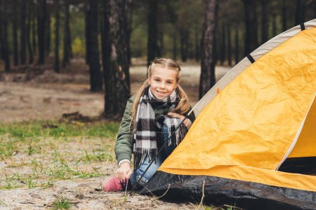child installing camping tent