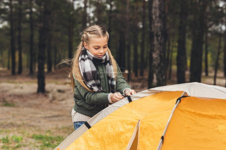 kid installing camping tent
