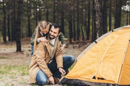 father and daughter installing tent