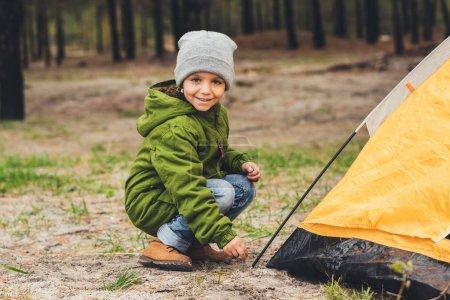boy sitting near camping tent