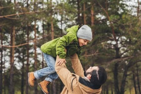 Photo for Father throwing up his happy little son in pine forest - Royalty Free Image