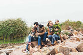 family sitting on rocky coast