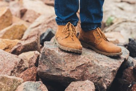 Photo for Cropped shot of man in stylish shoes standing on rocks - Royalty Free Image
