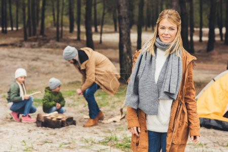 Photo for Happy woman looking at camera while her husband and kids making campfire on nature - Royalty Free Image