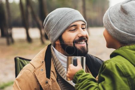 father and son with cup of hot drink