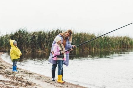 Mother and kids fishing together