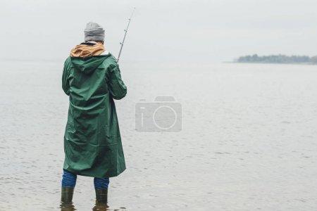 Photo pour Homme seul pêche le jour de l'automne pluvieux - image libre de droit