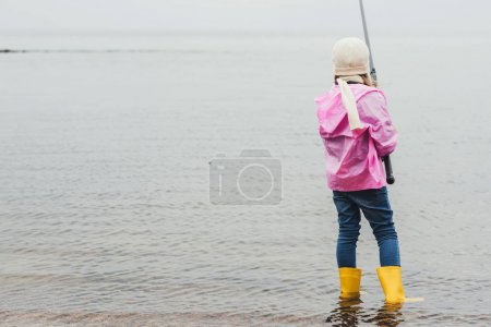 Photo for Back view of lonely little girl fishing in sea - Royalty Free Image