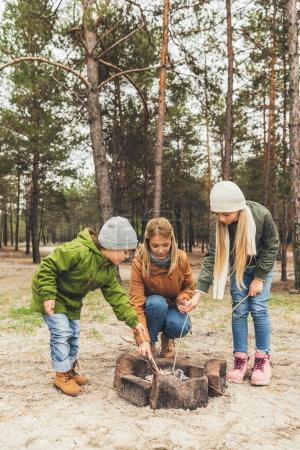 Mother and kids making bonfire