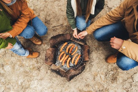 Family grilling sausages on bonfire