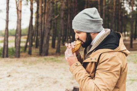 Man eating sandwich outdoors