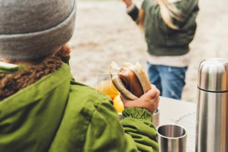 boy holding hot dog outdoors
