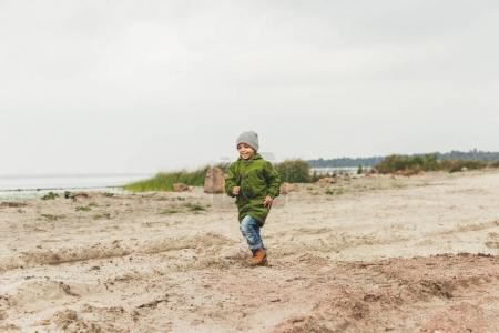 boy running by sandy beach