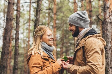 Photo for Happy couple touching beautiful moss at forest on cold autumn day - Royalty Free Image