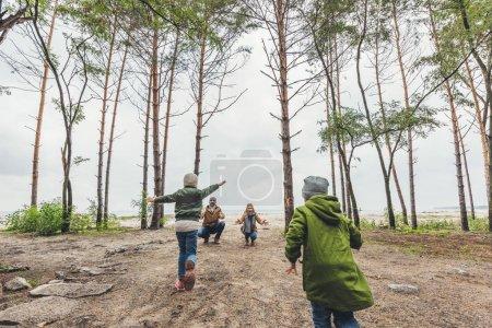 Photo pour Les petits enfants en cours d'exécution aux heureux parents nature - image libre de droit