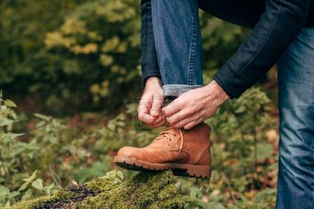 Man tying shoelaces in park