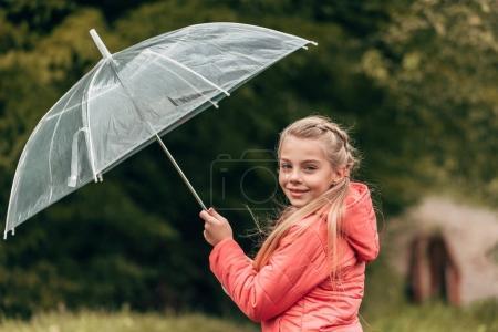 child with umbrella in autumn park
