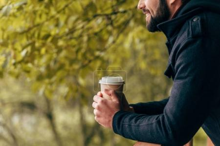 man with paper cup in park