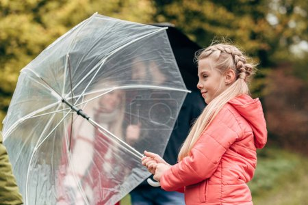 Parents and daughter with umbrellas