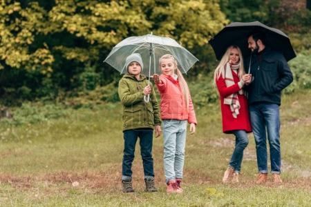 Photo pour Adorables petits enfants et jeunes parents tenant des parasols dans le parc d'automne - image libre de droit