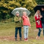 Постер, плакат: Parents and kids with umbrellas