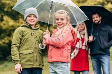 parents and kids with umbrellas