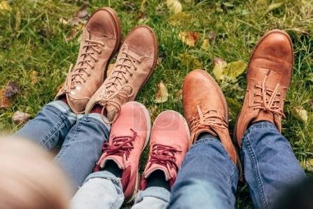 Photo for Cropped shot of family in autumn shoes sitting together in autumn park - Royalty Free Image