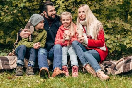 Family with paper cups in park