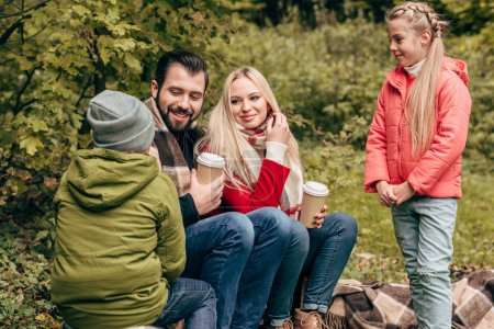 Family with coffee to go in park