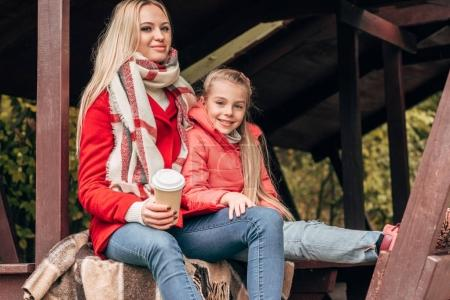 Mother and daughter with paper cup