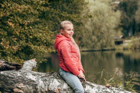 Child sitting on log in park