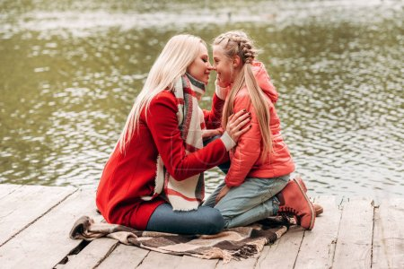 mother and daughter sitting near lake