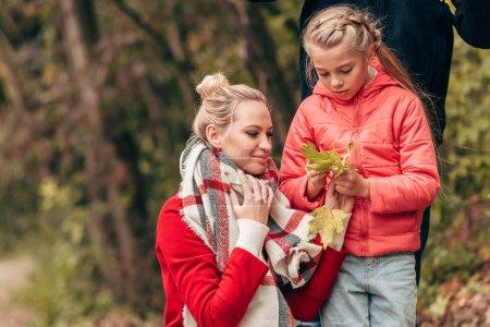 Photo pour Belle mère heureuse et fille tenant des feuilles jaunes dans le parc d'automne - image libre de droit
