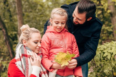 family holding autumn leaves in park