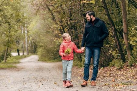 father and daughter walking in park