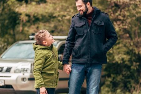 Photo pour Heureux père et fils se tenant la main et se souriant dans le parc - image libre de droit