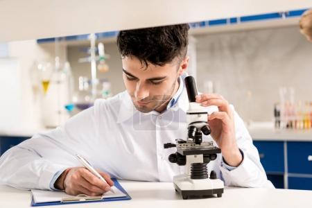 technician using microscope in laboratory
