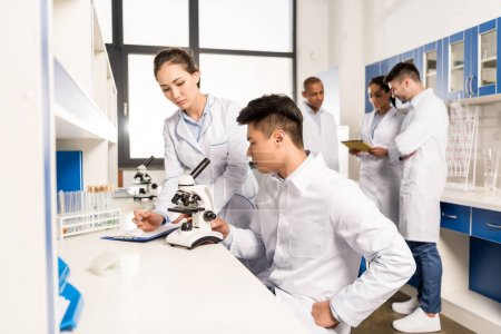 technicians working with microscope
