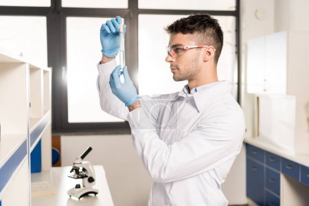 Photo for Serious young scientist in protective goggles holding test tube in research laboratory - Royalty Free Image