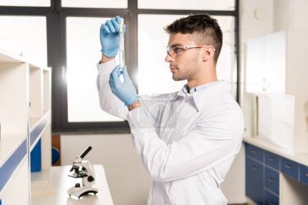 Photo pour Jeune scientifique sérieux dans des lunettes de protection tenant un tube à essai dans un laboratoire de recherche - image libre de droit