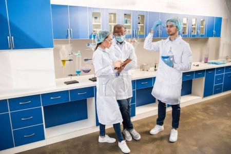 Photo for Scientist in protective wear examining test tubes with blue liquid at laboratory with colleagues taking notes - Royalty Free Image